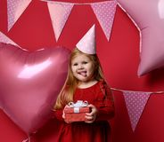 Adorable pretty girl with pink balloons and red present gift and birthday cap Royalty Free Stock Photo