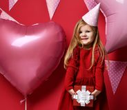 Adorable pretty girl with pink balloons and red present gift and birthday cap Stock Photos