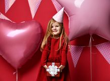 Adorable pretty girl with pink balloons and red present gift and birthday cap Stock Images