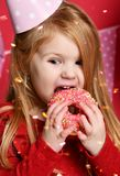 Adorable pretty girl with pink balloons and red present gift and birthday cap Royalty Free Stock Image