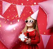 Adorable pretty girl with pink balloons and red present gift and birthday cap Royalty Free Stock Photography
