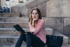 Adorable pretty student sits on stairs with laptop stock images