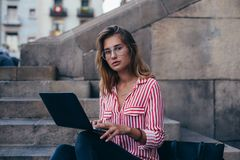 Adorable pretty student sits on stairs with laptop. Serious and concentrated young woman, in fashion trendy outfit sits on stairs of office building or stock photo