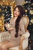Adorable pretty teen girl with gift box over Christmas backgroun. D. Happy funny brunette with long braid hairstyle sitting on modern armchair by mirrior with Stock Images