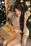 Adorable pretty teen girl with gift box over Christmas backgroun. D. Happy funny brunette with long braid hairstyle sitting on modern armchair by mirrior with Stock Image