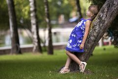 Adorable pretty young child girl with beautiful long blond hair in fashionable blue dress leaning on growing tree trunk smiling royalty free stock images
