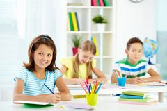 Adorable pupils. Image of cute school kids sitting at their workplaces and doing the tasks royalty free stock photo