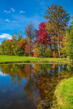 Adorable pure pond in the beautiful park. Concept of active tourism. Red, orange and green autumn foliage is reflected to clear water of the lake Royalty Free Stock Photo
