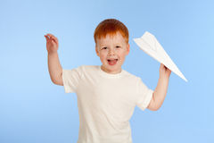 Adorable red-haired boy with paper plane model Stock Image