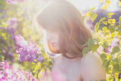 Adorable red-haired girl in spring blossoming garden Stock Photos