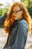 Adorable red haired young mpdel in glasses posing at the park Stock Photo