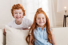Adorable redhead sister and brother sitting together on sofa at home Royalty Free Stock Photo