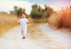 Adorable redhead toddler baby boy in jumpsuit running along rural summer road in sunburned field. Adorable cute redhead toddler baby boy in jumpsuit running Royalty Free Stock Photo