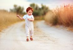 Adorable redhead toddler baby boy in jumpsuit running along rural summer road in sunburned field. Adorable cute redhead toddler baby boy in jumpsuit running Stock Image