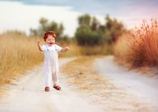 Adorable redhead toddler baby boy in jumpsuit running along rural summer road in sunburned field. Adorable cute redhead toddler baby boy in jumpsuit running Stock Photo