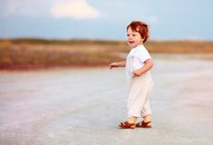 Adorable redhead toddler baby boy in jumpsuit walking through the summer road and field. Adorable cute redhead toddler baby boy in jumpsuit walking through the royalty free stock photography
