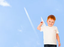 Adorable redheaded boy with paper plane on sky Stock Image