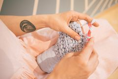 Adorable relaxed knitting crochet hobby. Woman in pink dress. leisure creation of clothes. Royalty Free Stock Photos