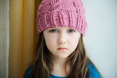 Adorable sad child girl in pink knitted hat Stock Photos
