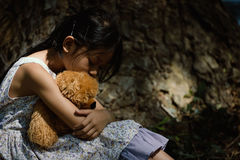 Adorable sad girl with teddy bear in park, Little girl is huggin Stock Images