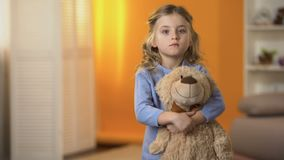 Adorable sad little girl hugging favorite teddy bear feeling lonely in orphanage