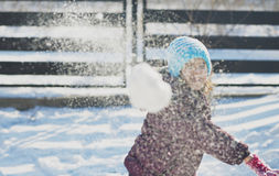 Adorable school aged kid girl in colorful sweater and hat playing in the snow on beauty winter day Royalty Free Stock Photo