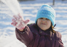 Adorable school aged kid girl in colorful sweater and hat playing in the snow on beauty winter day Royalty Free Stock Photos