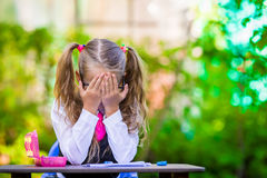 Adorable school girl at desk with notes and Royalty Free Stock Photography