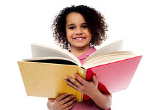 Adorable school girl reading a book with a smile. Smiling cute school girl reading a book, preparing for examinations Royalty Free Stock Photo