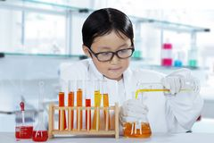 Adorable schoolboy experimenting chemical liquid. Portrait of an adorable schoolboy experimenting chemical liquid while standing in the laboratory Stock Image