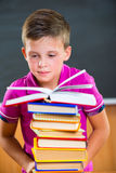 Adorable schoolboy with stack of books Royalty Free Stock Photo