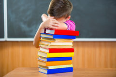 Adorable schoolboy with stack of books Stock Photo