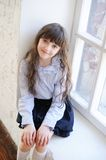 Adorable schoolchild sitting by the window Royalty Free Stock Images