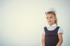 Adorable schoolgirl thinking in uniform Stock Photo