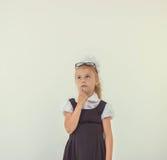 Adorable schoolgirl thinking in uniform Stock Photography