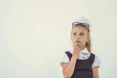 Adorable schoolgirl thinking in uniform Royalty Free Stock Photos