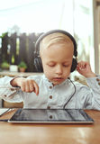 Adorable serious little boy choosing a soundtrack Royalty Free Stock Photography