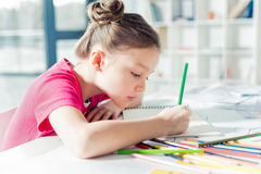 Adorable serious little girl sitting at table and drawing Stock Photos