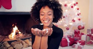 Adorable woman blowing out confetti. From her hands into camera direction. She sitting in front of fireplace and fully decorated white Christmas in her home stock footage