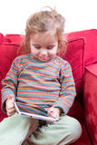 Adorable shy little girl with a tablet-pc Royalty Free Stock Photos
