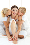Adorable siblings kissing their mother Stock Photo