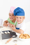 Adorable siblings kneading together a dough Royalty Free Stock Image
