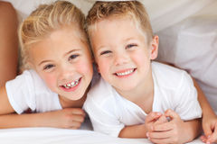 Adorable siblings playing on a bed Royalty Free Stock Photos