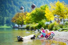 Free Adorable Sisters Playing By Konigssee Lake In Germany On Warm Summer Day. Cute Children Having Fun Feeding Ducks And Throwing Ston Stock Photography - 113305162