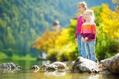 Adorable sisters playing by Konigssee lake in Germany on warm summer day. Cute children having fun splashing water and throw