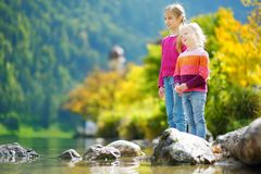 Adorable sisters playing by Konigssee lake in Germany on warm summer day. Cute children having fun feeding ducks and throwing ston Stock Photography