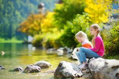 Adorable sisters playing by Konigssee lake in Germany on warm summer day. Cute children having fun feeding ducks and throwing ston Stock Photos