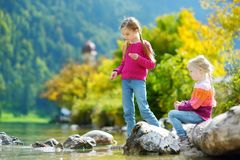 Adorable sisters playing by Konigssee lake in Germany on warm summer day. Cute children having fun feeding ducks and throwing ston Stock Photo