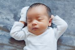 adorable sleeping Asian Chinese mixed race newborn baby girl boy lying on bed