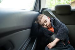 Adorable sleeping child on the back seat of the car with safety belt Stock Photo
